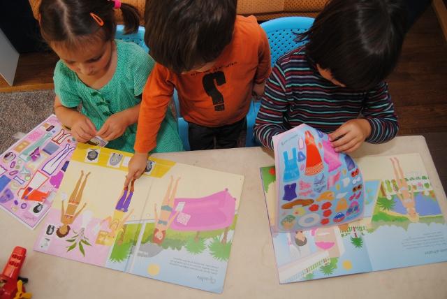 Kinderen spelen met stickerboeken